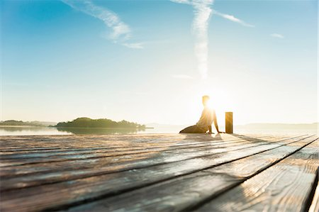 Young man sitting on pier of sunlit lake, Woerthsee, Bavaria, Germany Stock Photo - Premium Royalty-Free, Code: 649-08238160