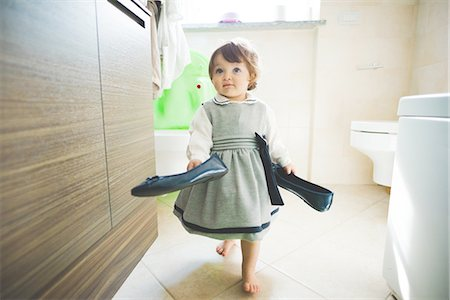 Female toddler carrying ladies shoes at home Stock Photo - Premium Royalty-Free, Code: 649-08238402