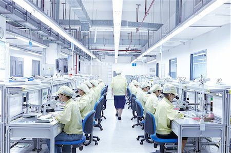 supervising - Supervisor overseeing quality check station at factory producing flexible electronic circuit boards. Plant is located in the south of China, in Zhuhai, Guangdong province Stock Photo - Premium Royalty-Free, Code: 649-08238654