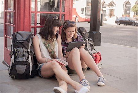 Two women backpackers sitting on sidewalk planning route on digital tablet, London, UK Stock Photo - Premium Royalty-Free, Code: 649-08238744