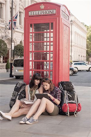 quaint - Two women backpackers sitting on sidewalk using digital tablet, London, UK Stock Photo - Premium Royalty-Free, Code: 649-08238743