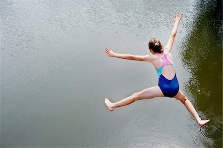 Overhead view of girl jumping into lake Stock Photo - Premium Royalty-Free, Code: 649-08238769