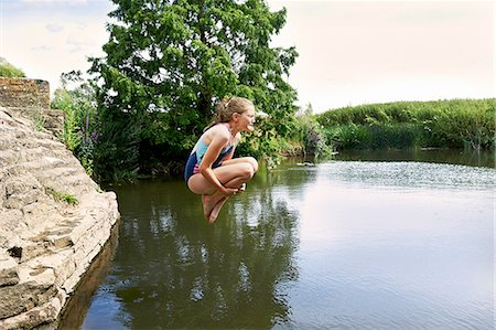 Side view of girl jumping into lake Stock Photo - Premium Royalty-Free, Code: 649-08238762
