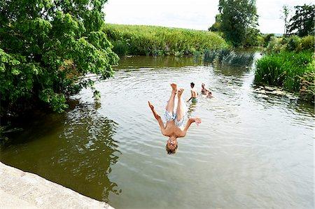 Teenage boy somersaulting into rural lake Stock Photo - Premium Royalty-Free, Code: 649-08238773