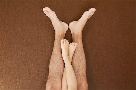 Child's legs on man's legs Stock Photo - Premium Royalty-Free, Code: 649-08238919