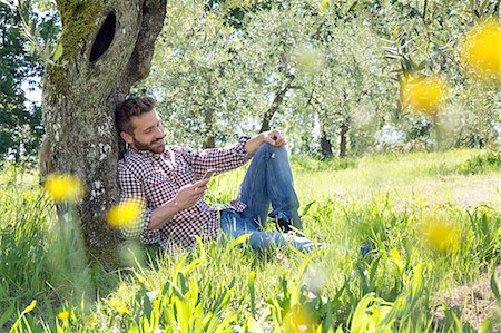 sitting under tree - Young man sitting leaning against tree using smartphone looking down smiling Stock Photo - Premium Royalty-Free, Code: 649-08239065