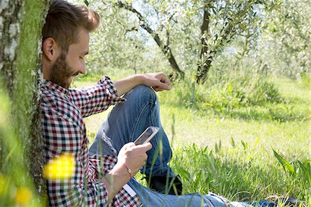 sitting under tree - Young man sitting leaning against tree using smartphone looking down smiling Stock Photo - Premium Royalty-Free, Code: 649-08239066