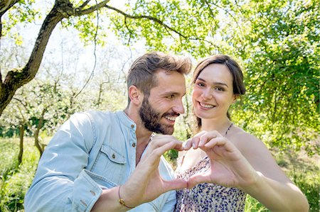 Young couple making heart shape with hands, looking at camera smiling Stock Photo - Premium Royalty-Free, Code: 649-08239088