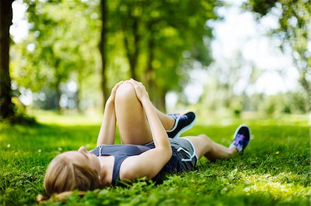 preteen girls stretching - Young girl in park, lying on grass, stretching legs Stock Photo - Premium Royalty-Free, Code: 649-08232449