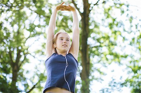 preteen girls stretching - Young girl in park, stretching arms, low angle view Stock Photo - Premium Royalty-Free, Code: 649-08232451