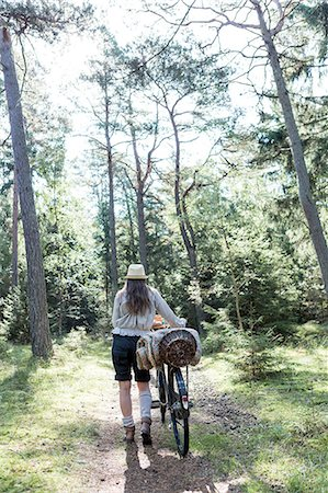 pushing - Mature woman pushing bicycle with foraging baskets on forest path Stock Photo - Premium Royalty-Free, Code: 649-08232805