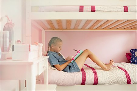 preteen girl pigtails - Side view of girl sitting on bunkbed writing in notebook Stock Photo - Premium Royalty-Free, Code: 649-08306394