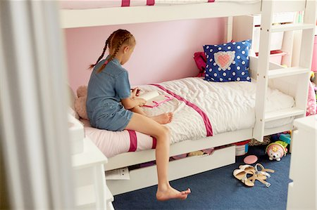 preteen girl pigtails - Rear view of girl sitting on bunkbed writing in notebook Stock Photo - Premium Royalty-Free, Code: 649-08306393