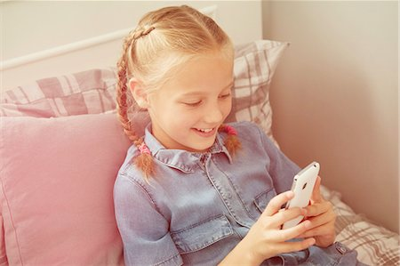 preteen girl pigtails - High angle view of girl sitting on bed looking down at smartphone smiling Stock Photo - Premium Royalty-Free, Code: 649-08306406