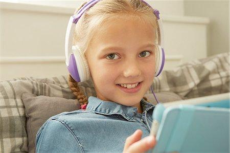 preteen girl pigtails - Girl wearing headphones holding digital tablet looking at camera smiling Stock Photo - Premium Royalty-Free, Code: 649-08306400