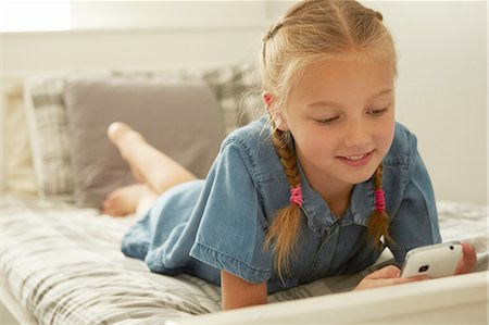 preteen girl pigtails - Girl lying on bed looking down at smartphone smilinhg Stock Photo - Premium Royalty-Free, Code: 649-08306401