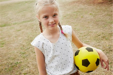 preteen girl pigtails - High angle view of girl with pigtails holding soccer ball looking at camera smiling Stock Photo - Premium Royalty-Free, Code: 649-08306417