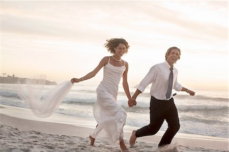 Bride and groom running on beach against sunset Stock Photo - Premium Royalty-Free, Code: 649-08306488