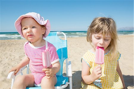 Female toddler and sister eating ice lollies on beach Stock Photo - Premium Royalty-Free, Code: 649-08306547