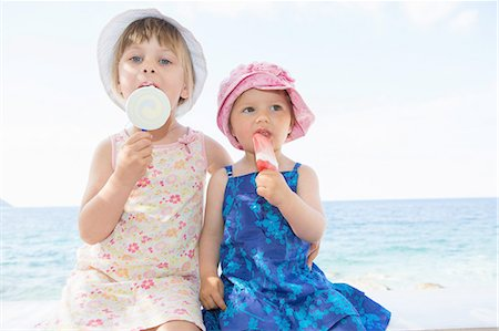 Female toddler and sister wearing sunhats eating ice lollies on beach Stock Photo - Premium Royalty-Free, Code: 649-08306552