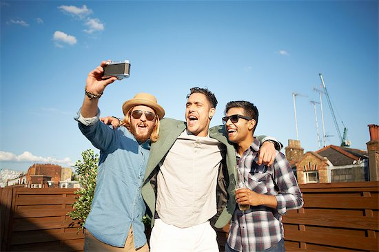 Three male friends taking camera selfie at rooftop party Stock Photo - Premium Royalty-Free, Image code: 649-08306640