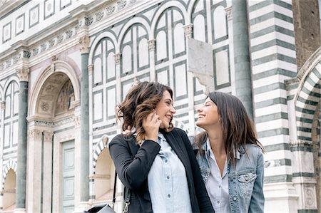 Lesbian couple using mobile phone face to face smiling, Piazza Santa Maria Novella, Florence, Tuscany, Italy Stock Photo - Premium Royalty-Free, Code: 649-08306696