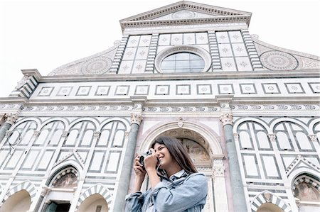 european - Low angle view of young woman using digital camera in front of church, Piazza Santa Maria Novella, Florence, Tuscany, Italy Stock Photo - Premium Royalty-Free, Code: 649-08306700