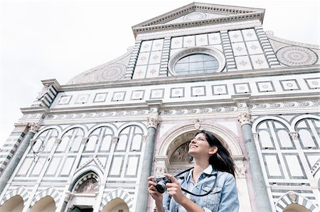 european - Low angle view of young woman using digital camera in front of church looking up, Piazza Santa Maria Novella, Florence, Tuscany, Italy Stock Photo - Premium Royalty-Free, Code: 649-08306701