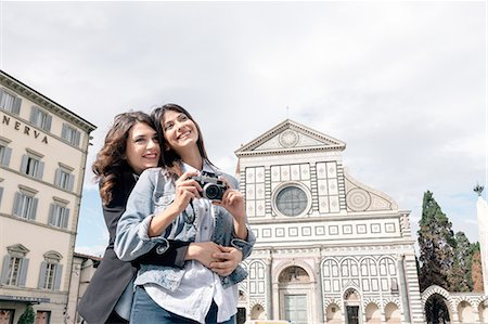 Lesbian couple holding digital camera hugging in front of church, Piazza Santa Maria, Novella Florence, Tuscany, Italy Stock Photo - Premium Royalty-Free, Code: 649-08306703
