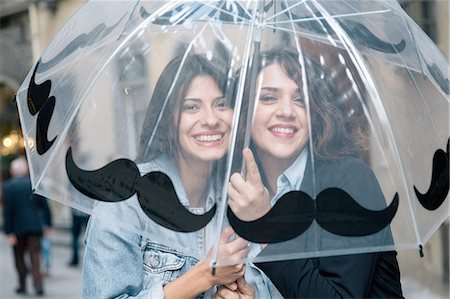 people with umbrellas in the rain - Lesbian couple underneath transparent umbrella looking at camera smiling, Florence, Tuscany, Italy Stock Photo - Premium Royalty-Free, Code: 649-08306737