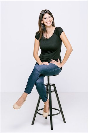 female - Young woman sitting on stool looking at camera smiling Stock Photo - Premium Royalty-Free, Code: 649-08306745