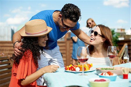 Male and female friends chatting at rooftop barbecue Stock Photo - Premium Royalty-Free, Code: 649-08306818