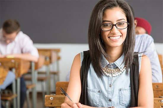 Portrait of female student, sitting at desk in classroom, smiling Stock Photo - Premium Royalty-Free, Image code: 649-08306874