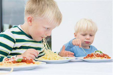 Boy and toddler brother eating spaghetti on patio Stock Photo - Premium Royalty-Free, Code: 649-08307424