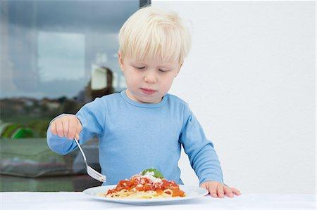 Male toddler eating spaghetti on patio Stock Photo - Premium Royalty-Free, Code: 649-08307423