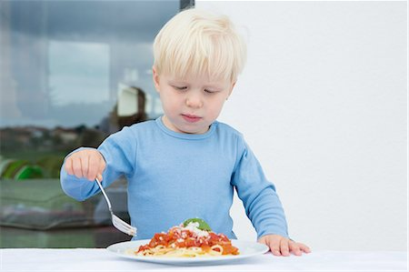 Male toddler eating spaghetti on patio Stock Photo - Premium Royalty-Free, Code: 649-08307423