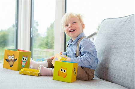 Portrait of happy male toddler playing with building blocks on sofa Stock Photo - Premium Royalty-Free, Code: 649-08307448