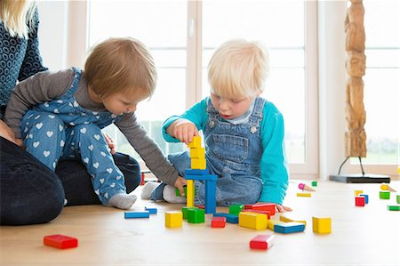 playing - Mid adult woman and two toddlers playing with building bricks on living room floor Stock Photo - Premium Royalty-Free, Code: 649-08307466