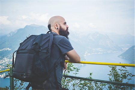 Mid adult man on balcony looking out at Lake Lugano, Switzerland Stock Photo - Premium Royalty-Free, Code: 649-08307479
