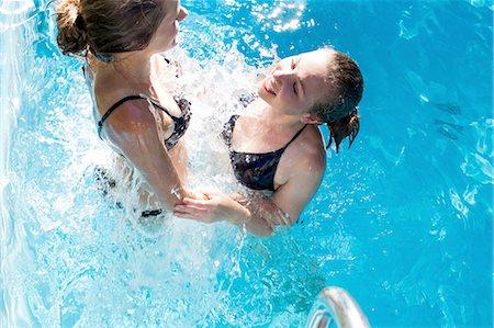 Teenage girls splashing in swimming pool Stock Photo - Premium Royalty-Free, Code: 649-08307512