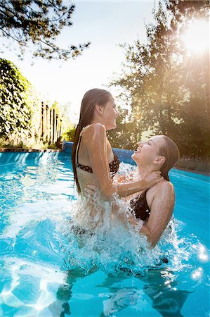 Two teenage girls jumping and splashing in swimming pool Stock Photo - Premium Royalty-Free, Code: 649-08307534