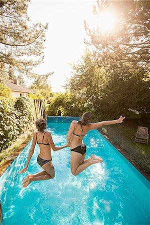 Two teenage girls jumping into swimming pool Stock Photo - Premium Royalty-Free, Code: 649-08307530