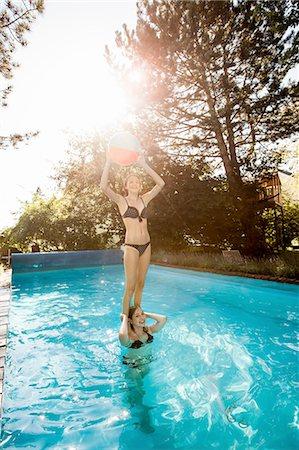 Teenage girl standing on best friends shoulders in swimming pool Stock Photo - Premium Royalty-Free, Code: 649-08307532