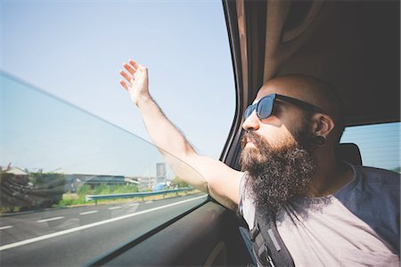 Bearded man sticking hand out of car window on highway, Garda, Italy Stock Photo - Premium Royalty-Free, Code: 649-08327628