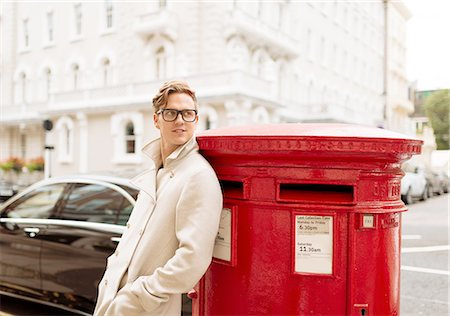 style - Stylish young man leaning against red post box, London, England, UK Stock Photo - Premium Royalty-Free, Code: 649-08328032