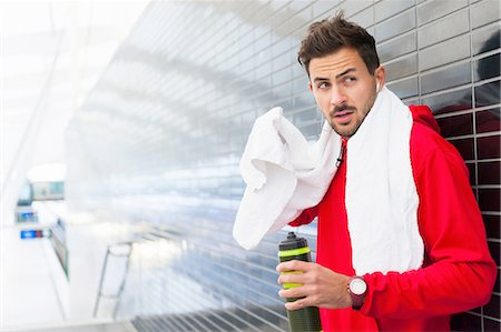 stock photograph - Sweating young male runner leaning against tiled wall drinking water Stock Photo - Premium Royalty-Free, Code: 649-08328078