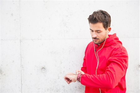 physical fitness - Young male runner in city checking smartwatch Stock Photo - Premium Royalty-Free, Code: 649-08328087