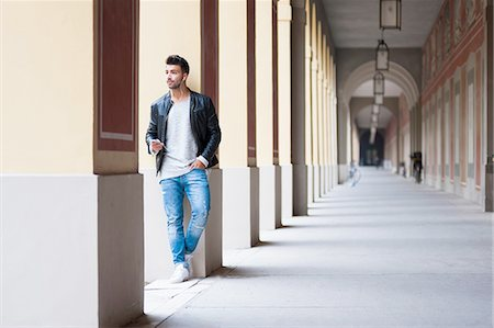 Young man daydreaming against column in colonnade Stock Photo - Premium Royalty-Free, Code: 649-08328164