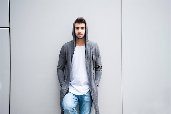 Young man leaning against grey wall with hands in pocket Stock Photo - Premium Royalty-Free, Image code: 649-08328170