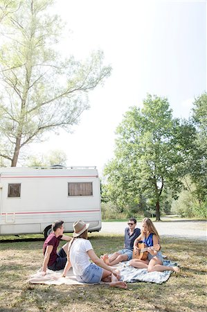 Group of young adults sitting on picnic blanket , relaxing, camper van in background Stock Photo - Premium Royalty-Free, Code: 649-08328214
